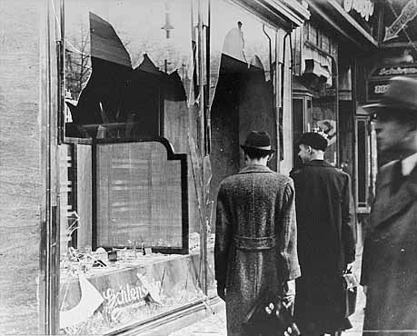 Germans pass broken window of Jewish-owned shop